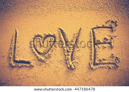 Text LOVE message handwritten on seashore sand. Valentine's day on the beach. Vignette and vintage picture style. Warm tone. - stock photo