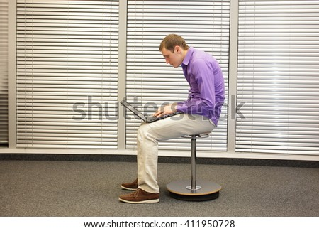 text neck - man in slouching position sitting on pneumatic stool, working with laptop in his office - stock photo