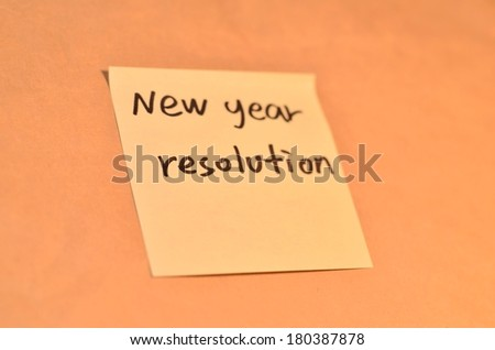 Text new year resolution on the short note texture background