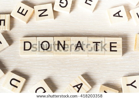 text of DONATE on cubes. Wooden abc. - stock photo