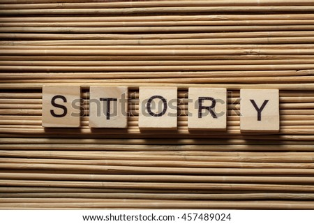 text of STORY on wood abc cubes at wooden background. - stock photo