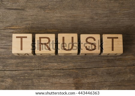 text of TRUST on a wooden cubes