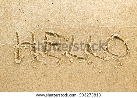 Text on sand on beach: hello