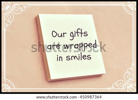 Text our gifts are wrapped in smiles on the short note texture background - stock photo