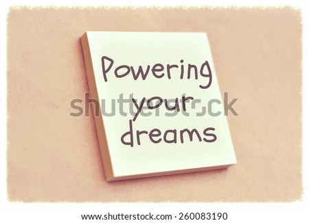 Text powering your dreams on the short note texture background - stock photo