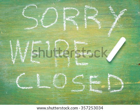 Text sorry we are closed written with chalk in old board  wooden.