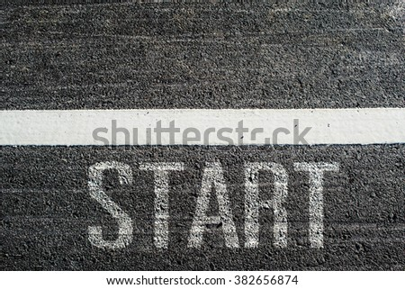 text START written on an asphalt road