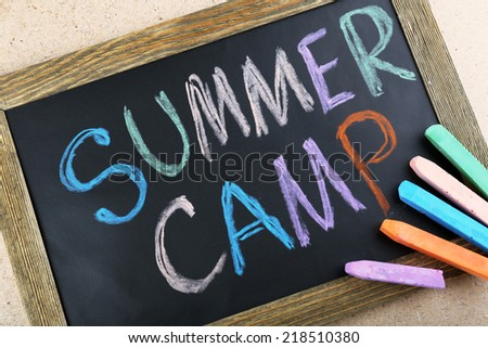 Text Summer camp written with chalk on chalkboard, and some chalk sticks of different colors - stock photo