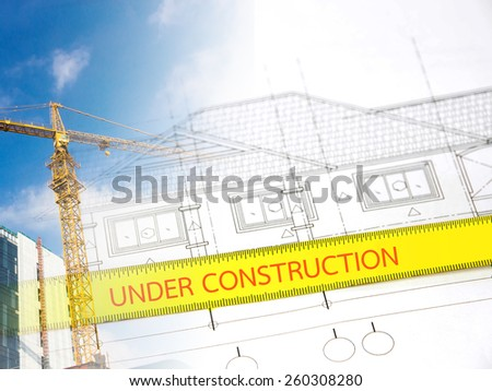 Text ''under construction'' in measuring tape over blurred architectural blueprint of office building - stock photo