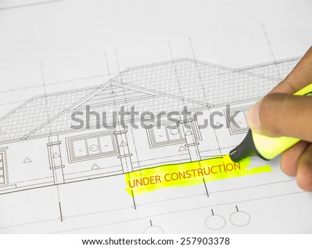 Text ''under construction''  over blurred architectural blueprint of office building - stock photo