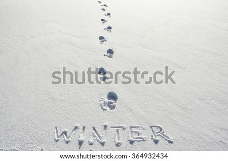 Text WINTER hand written on snow background and footsteps marks. Horizontal postcard template. - stock photo