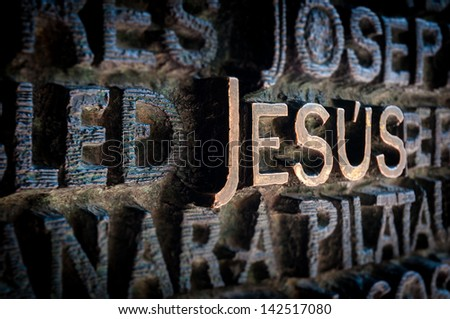 Text written with golden letters. Name Jesus standing out among other names of saints. Beautiful old wall of church in dark colours. Holy and religious place. Famous destination for tourists. - stock photo