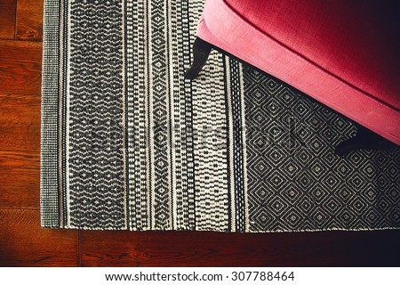 Textile armchair and knitted carpet - stock photo