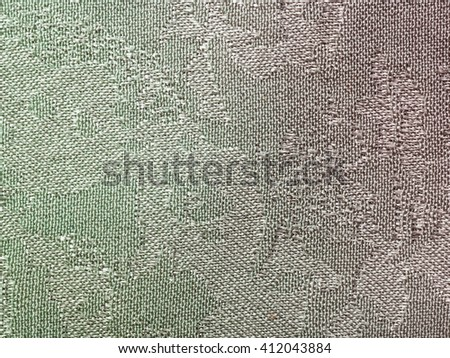 textile background - green and magenta colored batik silk fabric with Jacquard weave pattern of threads close up - stock photo