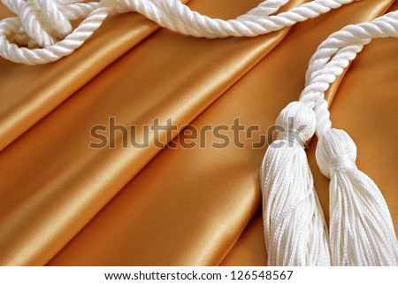 Textile background image of gold satin fabric with drapery cords (or graduation honor cords)