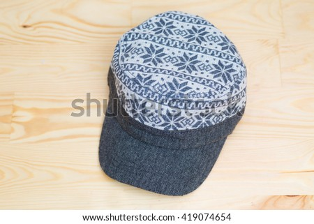 Textile cap onwooden background, Hipster wear - stock photo