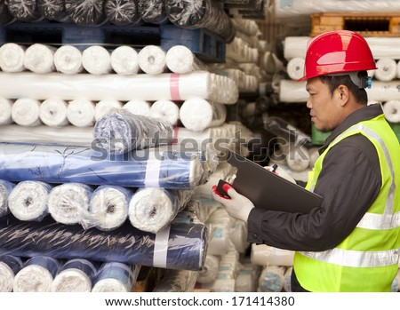 Textile factory foreman auditing raw material fabrics in warehouse - stock photo