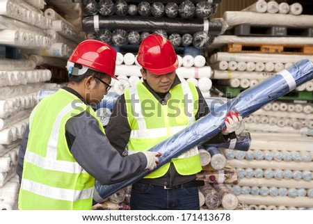 Textile factory workers checking fabric in warehouse