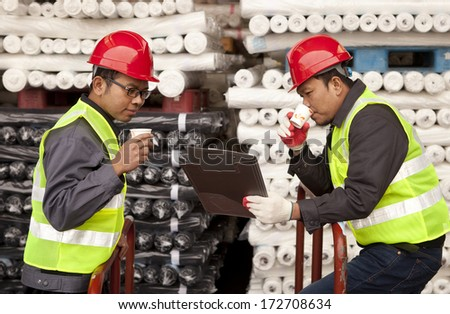 Textile factory workers discussing in warehouse fabric with drinking coffee