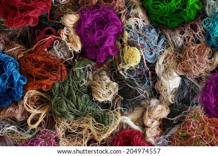 Textile industry background as a group of multi colored entangled sewing threads as a symbol for the fashion industry and clothing business or garment manufacturing as a heap of fibers.