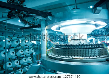Textile industry - yarn spools on spinning machine in a textile factory - stock photo
