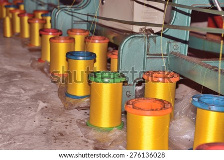 Textile industry �¢?? yarn spools on spinning machine in a textile factory - stock photo