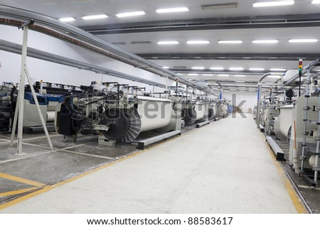 textile looms in a spinning and weaving factory, production hall in a yarn manufacturing factory - stock photo