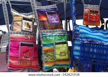 Textile shoulder bags with Ecuador print hanging from market stall