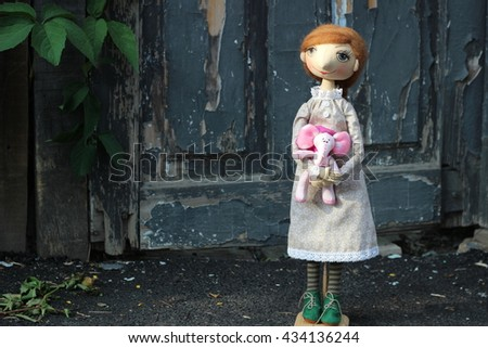 Textile toy doll with brunette hair and a pink toy elephant in the hands