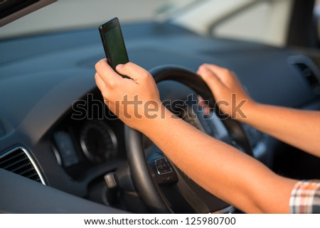 Texting and talking while driving, hands of young man on steering wheel - stock photo