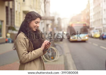 Texting brunette woman reads a message on her mobile phone and smiles while being unaware of approaching bus - stock photo