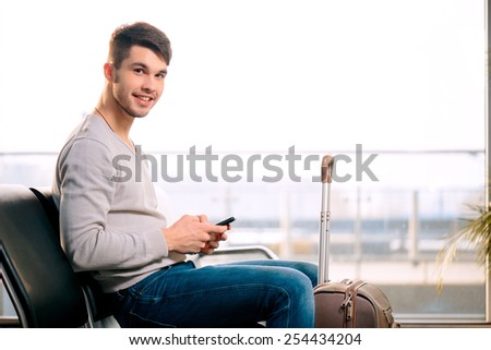 Texting he is fine. Portrait of handsome smiling man in casual wear holding his luggage and messaging through his mobile phone while sitting in the hall of the airport  - stock photo
