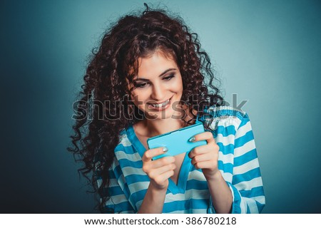Texting on phone. Beautiful, attractive girl playing on cellphone white dress silver pendant isolated blue background. Positive human face expression emotion feeling reaction perception body language - stock photo
