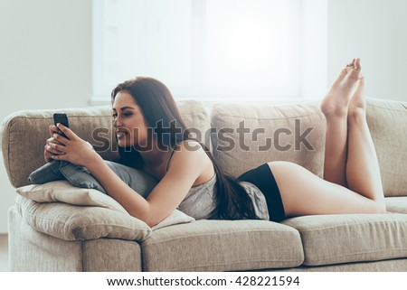 Texting to him. Beautiful young woman in panties and tank top holding smart phone and looking at it with smile while lying on couch at home - stock photo