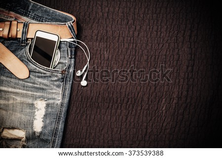 Texture background of jeans , belt detail with mobilephone and earphone in pocket and free copy space