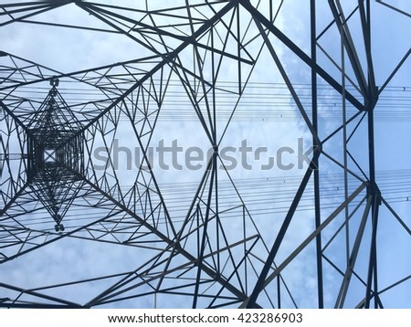 Texture energy pillars. Detail of electricity pylon against blue sky: high voltage electric pillar from below