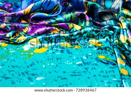 Texture, fabric, background. Women's scarf. Silk fabric is blue, floral pattern. Abstraction