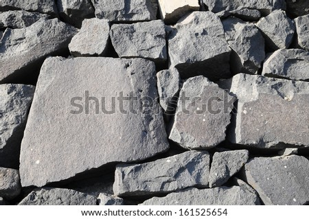 Texture Gray Rock Ancient Wall made of Volcanic Rocks  - stock photo