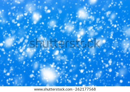 Texture made of snowflakes falling down with the blue sky in the background.