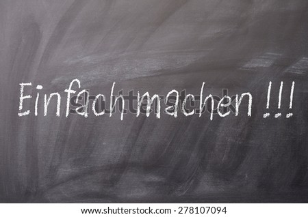 Texture of a blackboard with German words Just do it !