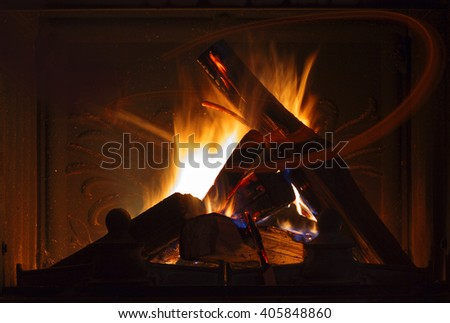 Texture of a blazing fire in the fireplace. Stone fireplace in a country house with fire, light painting.