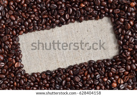 Texture of a gray canvas made of old and coarse burlap, on which lies a certain amount of brown coffee beans. Top view of sackcloth of light gray color under sunlight with pile of coffee beans