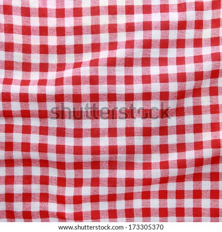Texture of a red and white checkered picnic blanket. Red linen crumpled tablecloth.