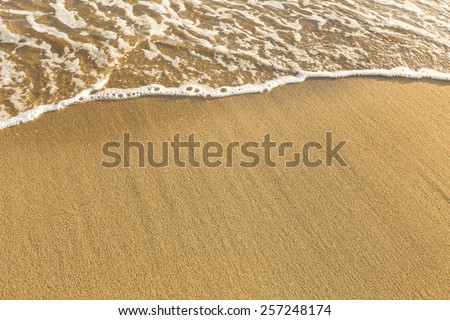Texture of beach sea sand with a soft wave of surf. - stock photo