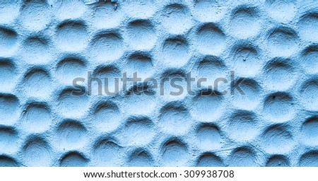 Texture of blue wall plastered in form of honeycombs