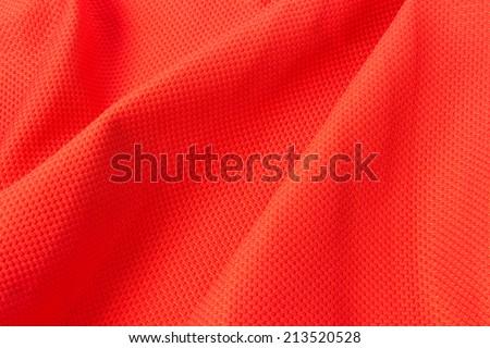 Texture of bright, acid rad cloth with pleats - stock photo