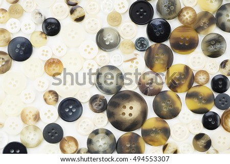 Texture of buttons in browns, white and black tones.