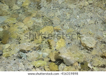 Texture of clear water with reflections and gray stones under water - stock photo
