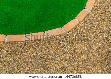 texture of gravel stone and green artificial grass partitioned with brick - stock photo