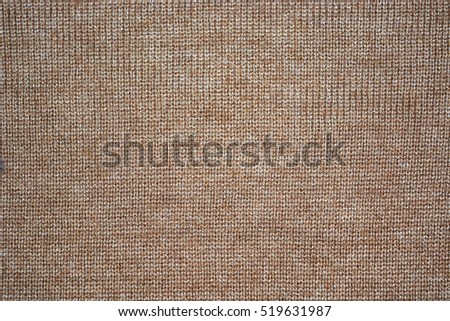 Texture of knitted woolen beige color of fabric for wallpaper and an abstract background.